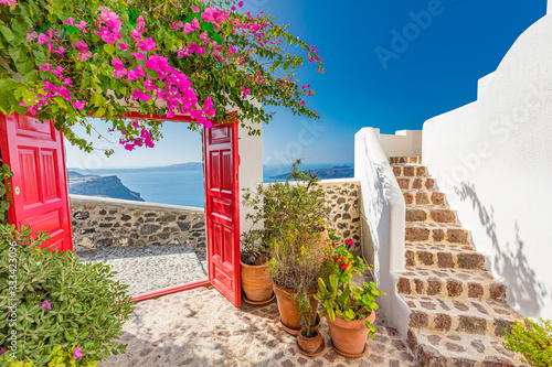Fantastic summer vacation landscape. Santorini white architecture with red gate and pink flowers. Tranquil travel background, luxury tourism scenery, stone stairs under blue sky.