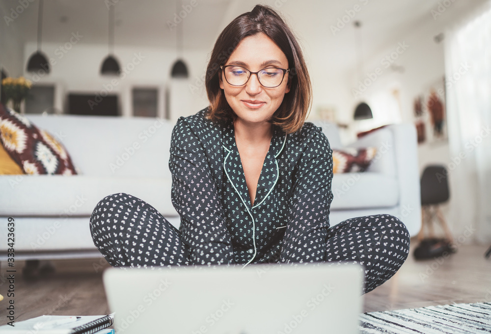 Fototapeta Smiling  Businesswoman dressed pajamas typing notebook keyboard chatting with colleagues sitting cross-legged on living room floor office with laptop.Distance work in worldwide quarantine time concept