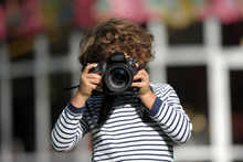 Child Learns To Take Pictures In A Park With A Professional Reflex Camera