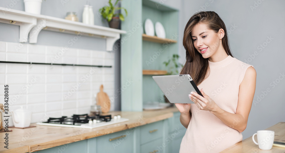 Fototapeta Beautiful young woman with digital tablet relaxing at home, Happy student girl using tablet pc in kitchen, Resting, relaxation, technology, online shopping, studying at home, learning online concept