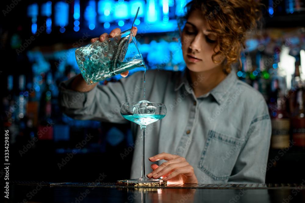Fototapeta pretty woman bartender accurate pour cocktail into glass