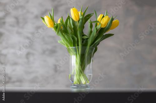 Fototapeta Bukiet żółtych tulipanów w wazonie na stole. obraz