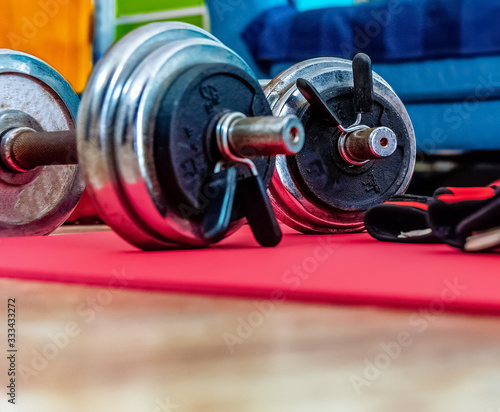 Fototapeta Close up of dumbbells on a yoga mat in an apartment floor obraz