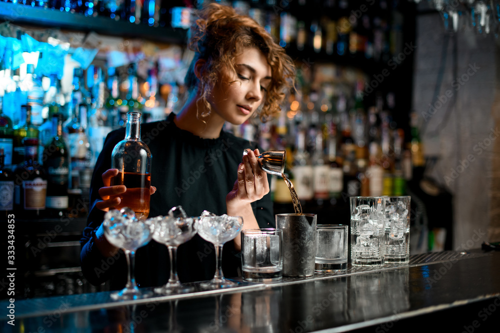 Fototapeta Young barman lady carefully pours drink into metal glass using jigger