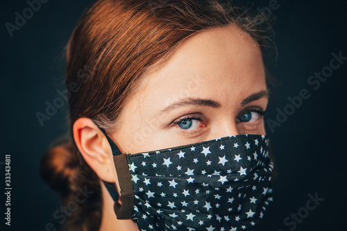 Fototapeta Close up woman portrait, Young woman wearing home made hygienic face medical mask to prevent infection, illness or flu and 2019-nCoV. Black background. Protection against disease, coronavirus. obraz