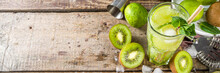 Summer Cold Drink And Beverages Recipes. Kiwi Lime Mojito Cocktail Or Non-allcohol Mocktail With Limes, Mint And Sliced Kiwi Fruits On Wooden Background Copy Space