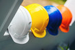 White, yellow and other colored safety helmets for workers' safety projects in the position of engineers or workers on concrete walls in the city.