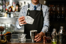 Bartender In Black Apron Holds...