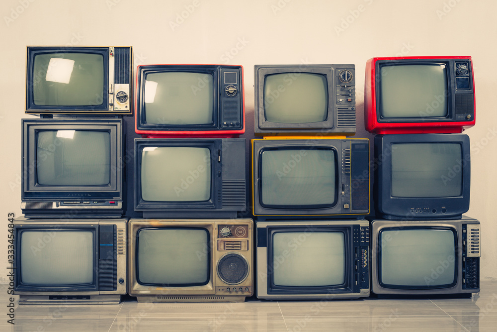 Retro old TVs pile on floor in the room. Television stack with vintage filter effect
