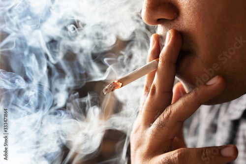 Carta da parati asian man smoking a cigarette smoke spread dark background