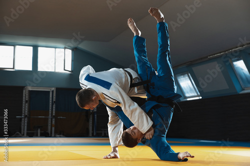 Two young judo caucasian fighters in white and blue kimono with black belts training martial arts in the gym with expression, in action, motion Poster Mural XXL