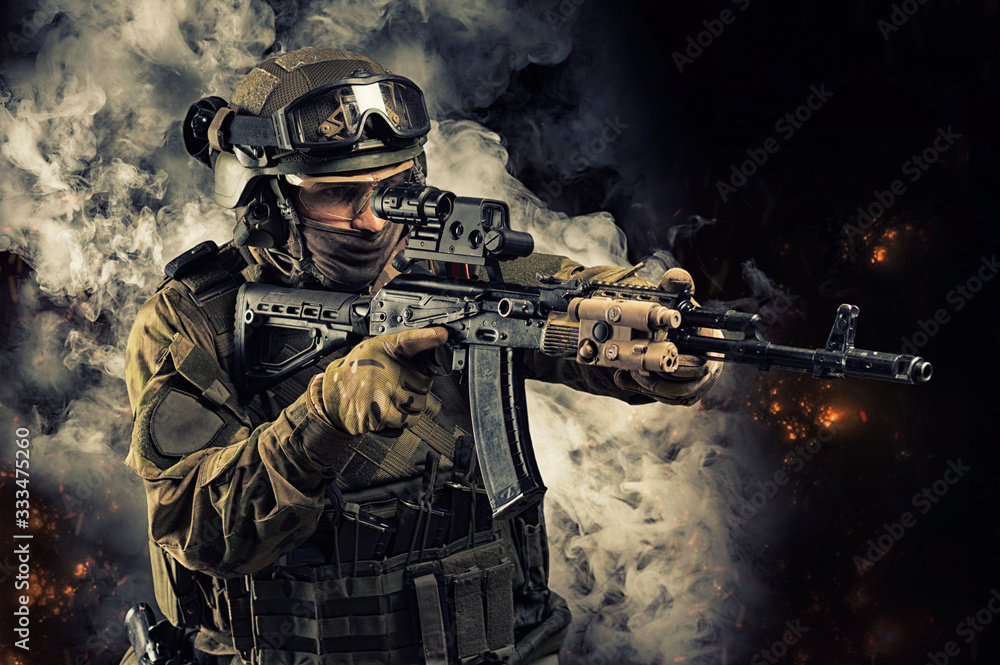 Fototapeta Portrait of a special forces soldier who is aiming at a collimator sight of a machine gun. The concept of special military units. Computer games.
