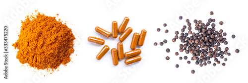 Fototapeta Pile of curcumin powder, Curcuma capsules and black peppercorns  isolated on white background. Health benefits and antioxidant food concept. Top view. Flat lay.  obraz