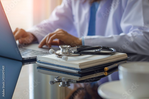 Canvas Print Female doctor in white lab coat typing on laptop computer with notebook and medical stethoscope on the desk at workplace