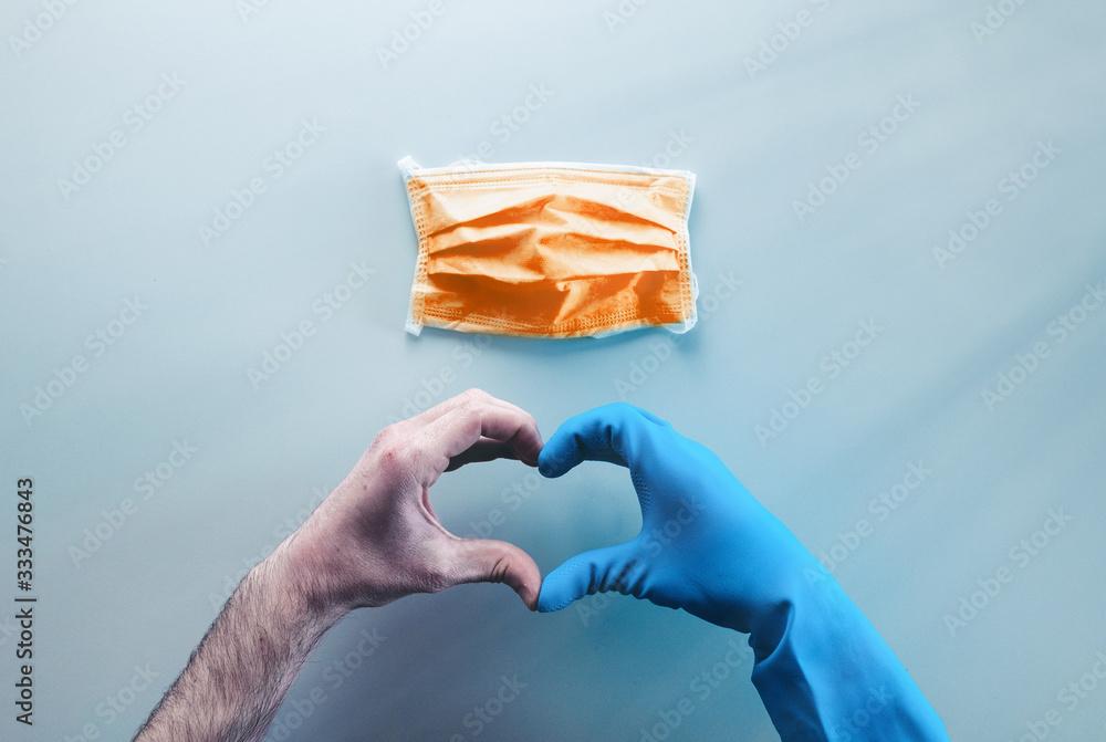 Fototapeta Coronavirus in Italia fine della pandemia, successo con simbolo del cuore fatto dalle mani di un medico. Virus definitivamente debellato. Vista alto, livello piatto.
