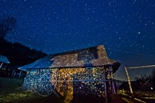 Bright Star Tracks In Clear Deep Blue Night Sky, Mysterious Landscape With Old Barn And Firewood, Carpathian Mountains In Transcarpathia, Wonder Of Nature Background
