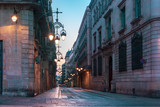 Fototapeta Uliczki - Narrow cobbled medieval empty street with beautiful street lights in Barri Gothic Quarter in the morning, Barcelona, Catalonia, Spain