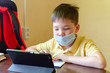Asian child boy student in medical face mask homework online lesson at home, epidemic Coronavirus, MERS-CoV, 2019-nCoV, quarantine, Covid-19 self-isolation, online education, home schooling