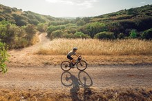 Cyclist Riding Gravel From Side In Golden Fields