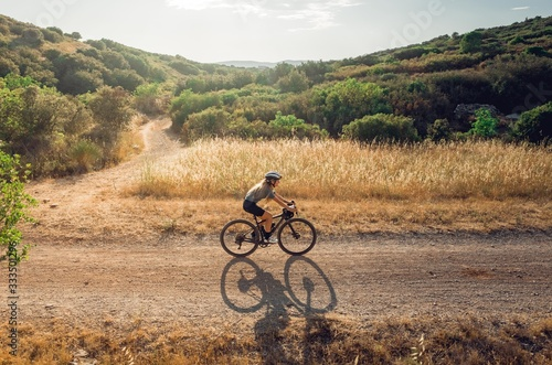 Cyclist riding gravel from side in golden fields Canvas Print