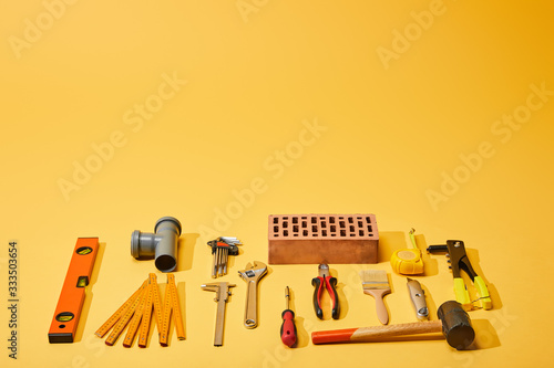 flat lay with industrial tools and brick on yellow background