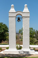 Stellenbosch, Western Cape, South Africa. Dec 2019. A Slave Bell Mounted Between Two White Painted Pillars On A Wine Farm In Stellenbosch, Western Cape, South Africa.