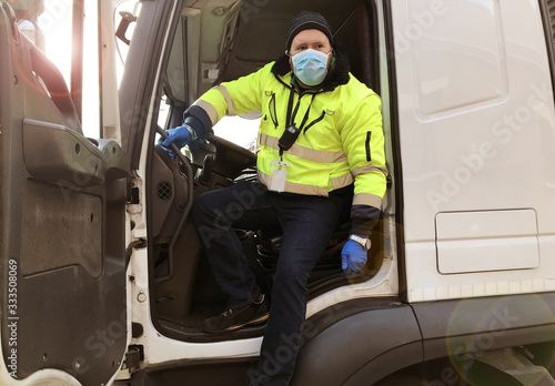Fotografie, Tablou young transporter on the truck with face mask and protective gloves for Coronavi