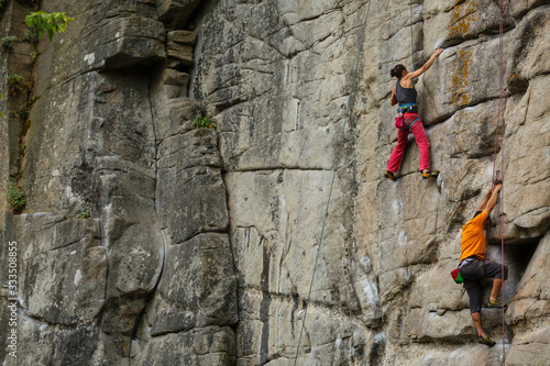 A young woman with a rope engaged in the sports of rock climbing on the rock Canvas Print