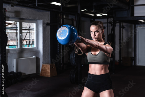 Fotografia, Obraz Young sweaty strong muscular fit girl holding heavy kettlebell with her hands an