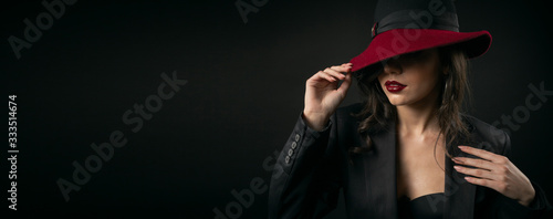 Elegant fashionable woman hiding face beneath hat touching brim and jacket, retr Wallpaper Mural