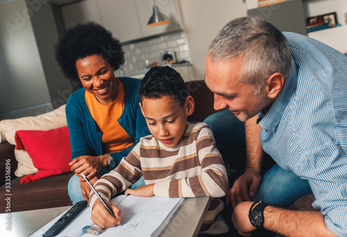 Obraz Parents helping their son with his homework at home in living room. - fototapety do salonu
