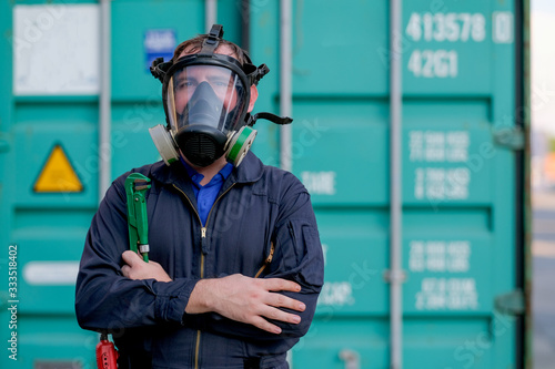 Fototapeta Technician or worker with chemical mask also engineer uniform stand and hold wrench in front of green container workplace and look confident by cross arms or fold over