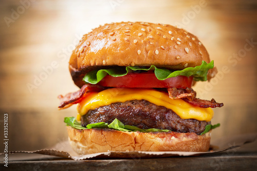 Fototapeta burger with cheese, bacon, salad and vegetables obraz