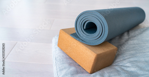 Obraz Yoga mat, cork block meditation pillow eco-friendly sustainable fitness products shopping. Natural organic material props for wellness on wooden floor background. - fototapety do salonu