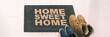 Home sweet home entrance door mat at condo floor with couples pairs of shoes moving in together. women's shoes and man's boots on floor, new apartment. Panoramic banner.