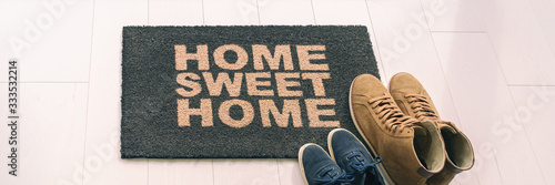 Obraz Home sweet home entrance door mat at condo floor with couples pairs of shoes moving in together. women's shoes and man's boots on floor, new apartment. Panoramic banner. - fototapety do salonu