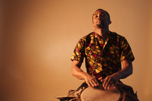 African American Man Musician Playing Traditional Drums At Brown Background Copy Space. Online Musical Class Learning Musical Instruments. Rhythm And Blues Style. Ethnic Culture And Traditions.