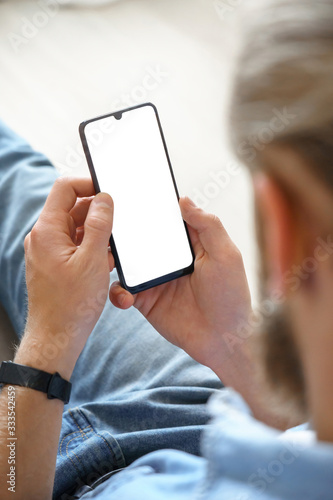 Millennial man user holding smart phone mock up white screen in hand using mobile dating app, check social media, order food delivery, reading news sit on couch at home. Over shoulder vertical view. - 333542459