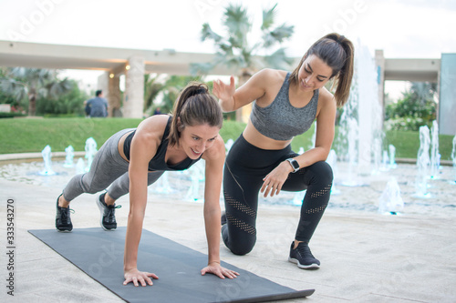 Tablou Canvas Fitness young woman doing push-ups with assistance of her female personal traine