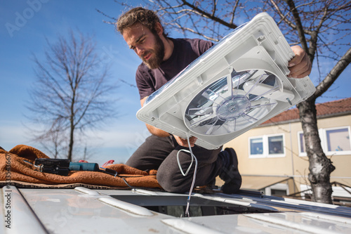 Photo Man installing a fan on the roof of his camper van