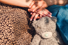 Toy Teddy Bear On The Background Of Human Hands.