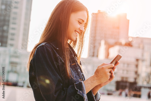 Fototapeta Young cheerful stylish woman using cell phone and texting message on city street. Beautiful happy hipster girl holding smart phone in hands and smiling. Surfing internet outdoors. Online communication obraz