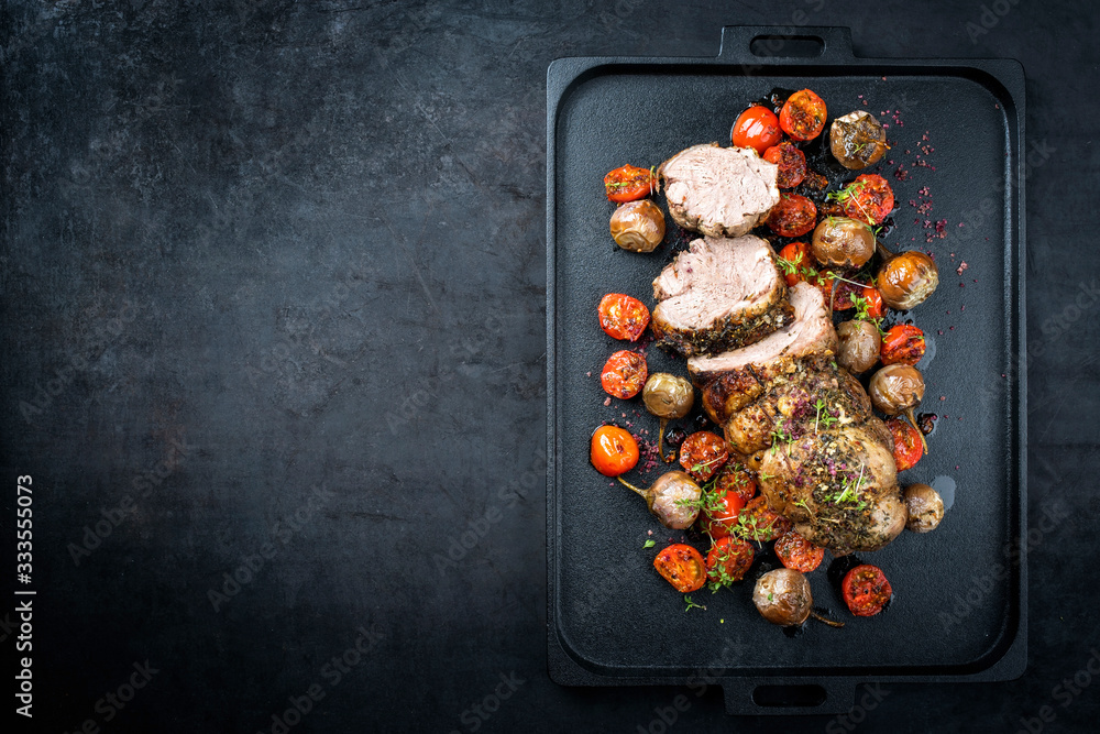 Fototapeta Traditional barbecue rolled lamb roast sliced with tomatoes and mini eggplant as top view on a modern design black tray with copy space left