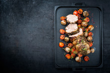 Traditional Barbecue Rolled Lamb Roast Sliced With Tomatoes And Mini Eggplant As Top View On A Modern Design Black Tray With Copy Space Left