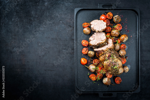 Fototapeta Traditional barbecue rolled lamb roast sliced with tomatoes and mini eggplant as top view on a modern design black tray with copy space left obraz