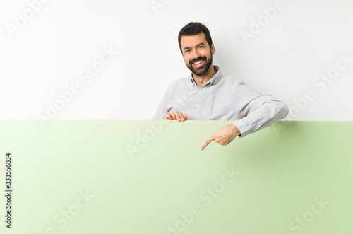 Young handsome man with beard holding a big green empty placard and pointing it Canvas-taulu