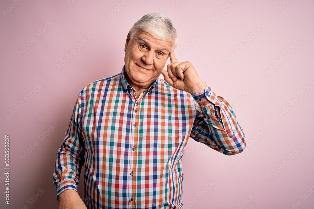 Fototapeta Senior handsome hoary man wearing casual colorful shirt over isolated pink background Smiling pointing to head with one finger, great idea or thought, good memory