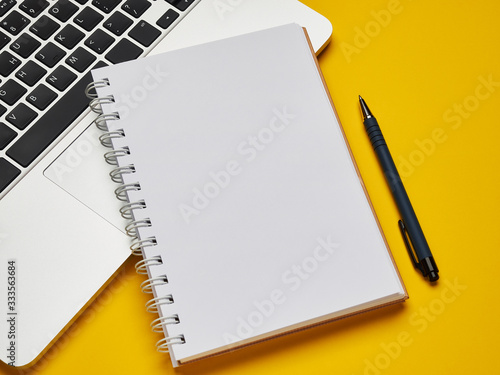 Workplace - laptop, notebook and pen for remote work on a yellow background table Fototapete