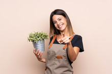 Young Woman Holding A Plant Points Finger At You With A Confident Expression
