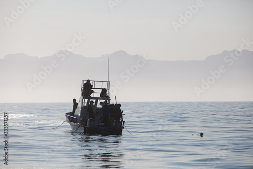A small boat with a film crew is found on the calm morning waters in False Bay, South Africa Canvas Print